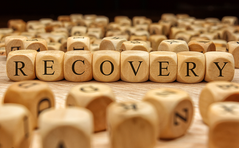 Letter tiles spell out recovery on a tabletop