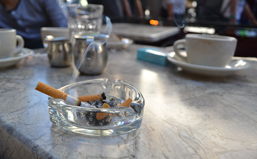Photo of a lit cigarette in a glass ashtray.