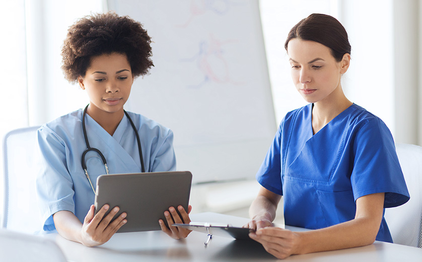 Two female medical professionals, seated at a round table, study an electronic pad with information.