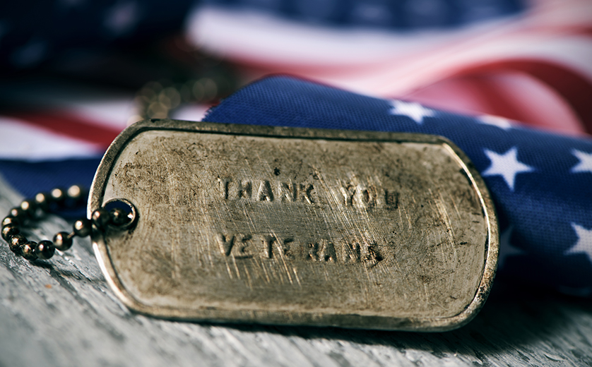 Picture of rusty dog tags against folded american flag