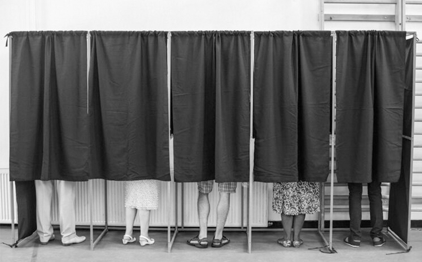 A diverse group of voters in curtained booths; black and white, lower legs visible