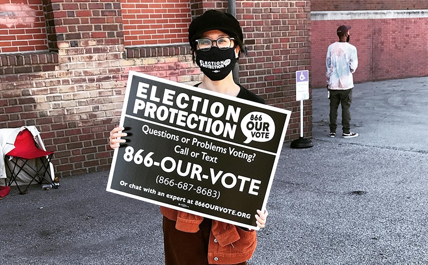 A volunteer outside a polling station during the November 3 election, holding a sign