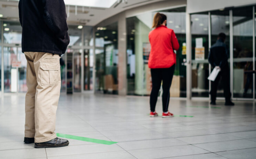 People in mall socially distanced, man standing behind green line