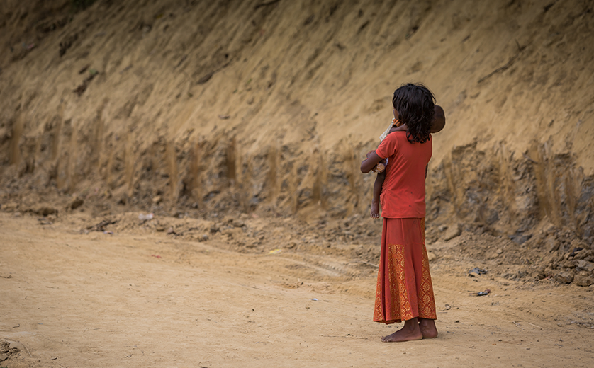 A young girl looks down a desert road in a refugee camp
