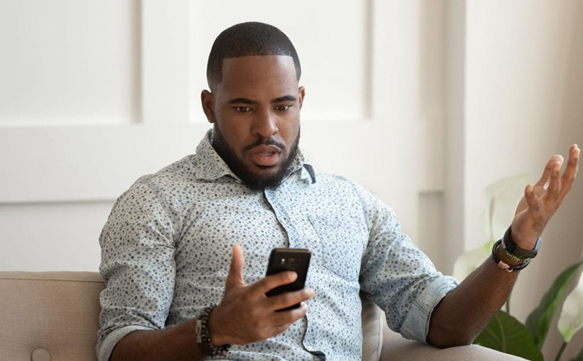 An African American man looks at his phone with a startled look on his face.