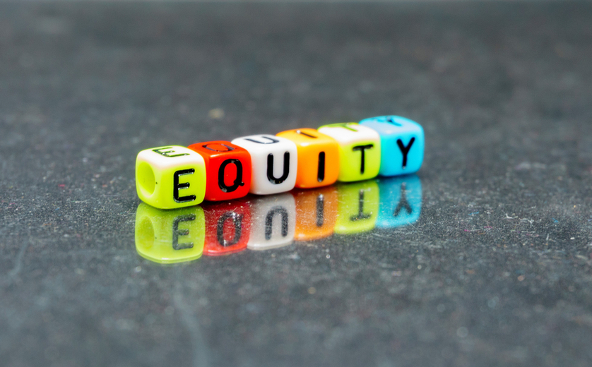 Colored blocks with letters on tabletop that spell 'equity'