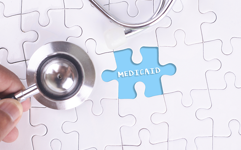 A puzzle with a piece missing; a hand holds the piece over a blue space with 'Medicaid' printed in whit