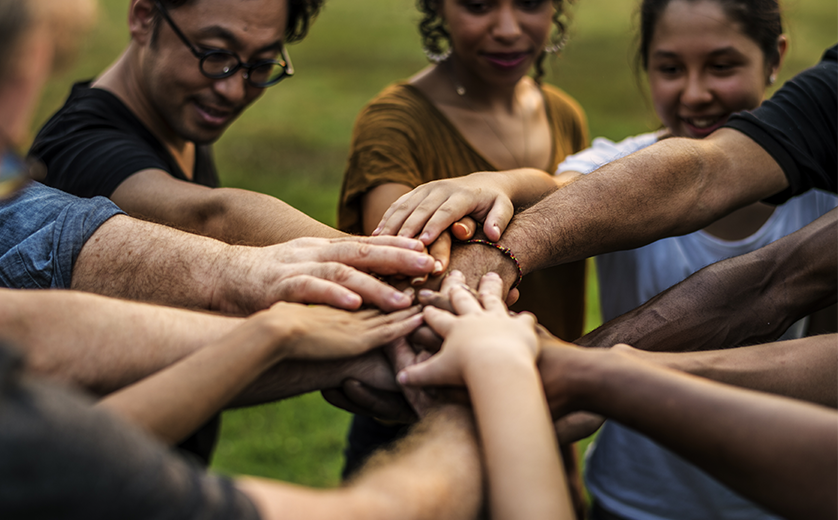 A group of people in a park, from differing ethnicities stand in a circle, hands in,